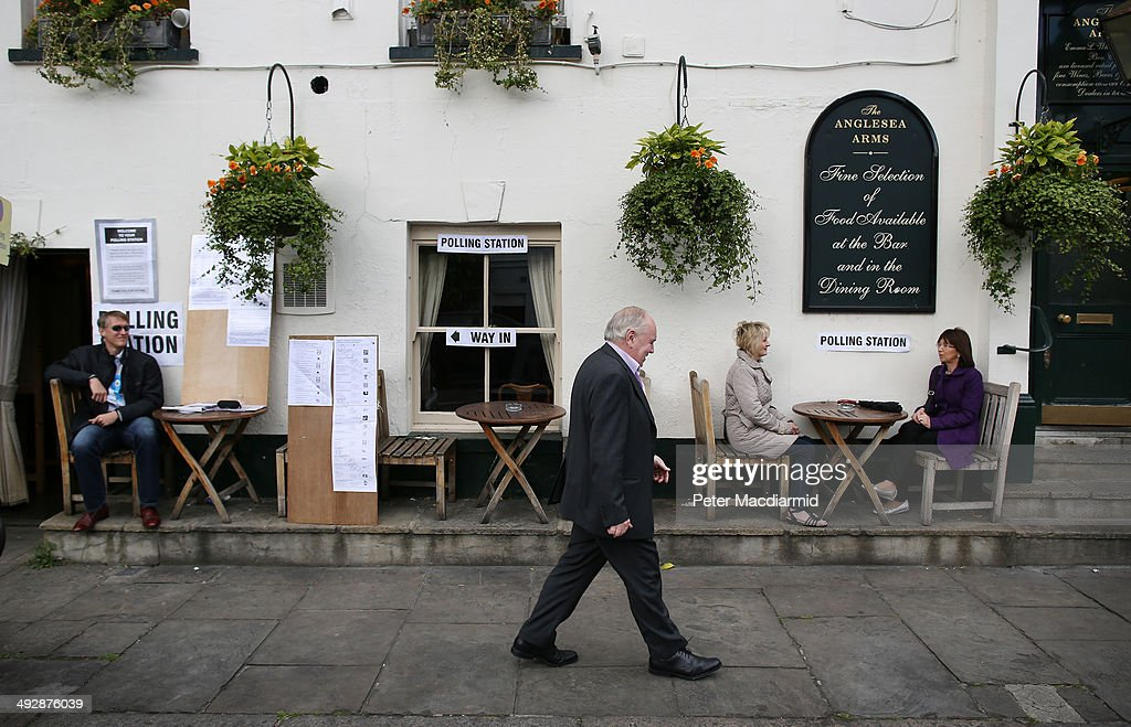 Women (R) wait for a friend who has gone to cast his vote inside The Anglesea Pub which is open as a polling station on May 22, 2014 in London, England. Millions of voters are going to the polls today in local and European elections.