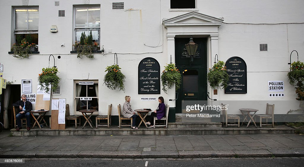 Women wait for a friend who has gone to cast his vote inside The Anglesea Pub which is open as a polling station on May 22, 2014 in London, England. Millions of voters are going to the polls today in local and European elections.