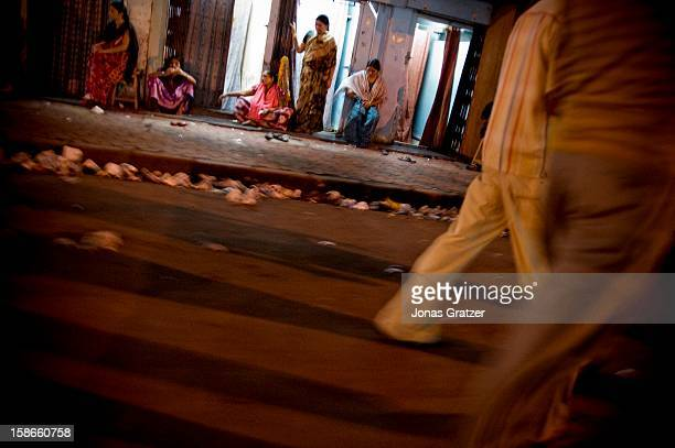 Women wait for customers outside a brothel in Kamathipura The price of sex has gone up since the British established the notorious Kamathipura as a...