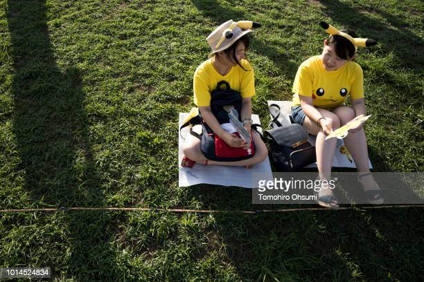 Women wait for performers dressed as Pikachu a character from Pokemon series game titles during the Pikachu Outbreak event hosted by The Pokemon Co...