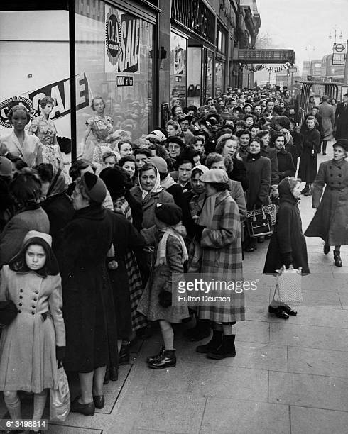 Women wait for the doors to open on a CA clothing store's January sale