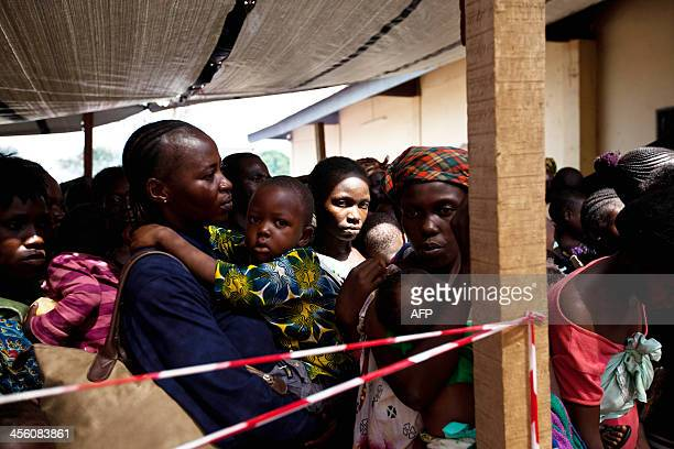 Women wait in a queue for medical assistance at the Medecins Sans Frontiers tent at a camp for Internally Displaced Peoples near the airport in...