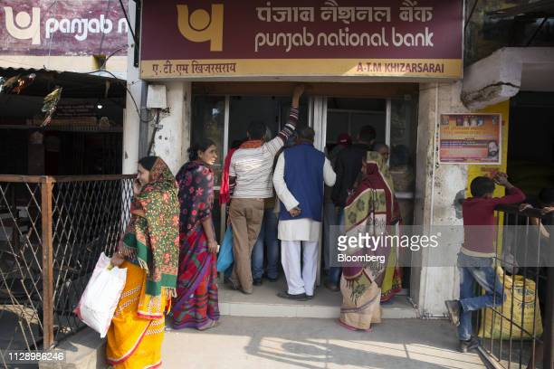 Women wait in line with other customers at a Punjab National Bank automated teller machine branch in Khizasarai Bihar India on Tuesday Jan 8 2019...