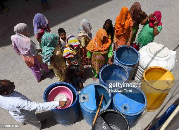Women wait in queue to fill water from a water tanker due to heavy water crisis at Harijan Basti Aya Nagar on June 19 2018 in New Delhi India