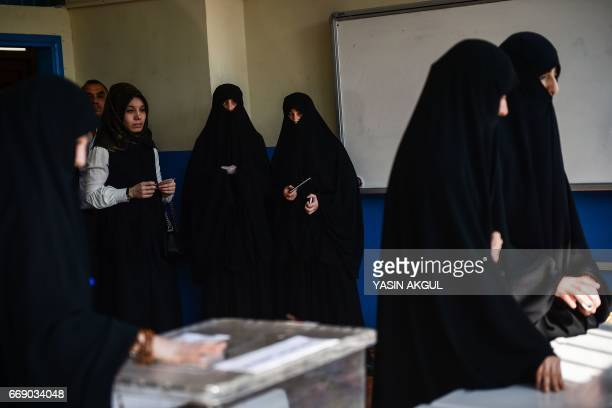 Women wait their turn to vote at a polling station during the referendum on expanding the powers of the Turkish president on April 16 2017 in Fatih...