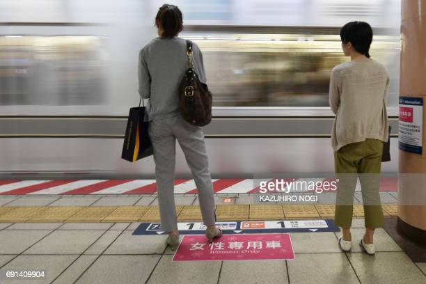 Women wait to board a women'sonly carriage onboard a train on a subway station platform in Tokyo on June 2 2017 In Japan where train travel can often...