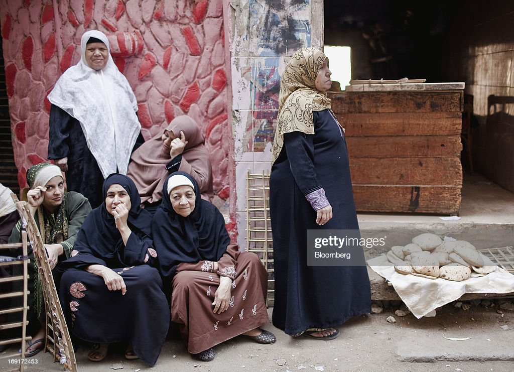 Women wait to buy bread outside a bakery in Cairo, Egypt, on Monday, May 20, 2013. Egypt will curb wheat imports by 31 percent to 8 million metric tons in 2012-13, still enough to make it the world's biggest buyer, the U.S. Department of Agriculture estimates. Photographer: Shawn Baldwin/Bloomberg via Getty Images