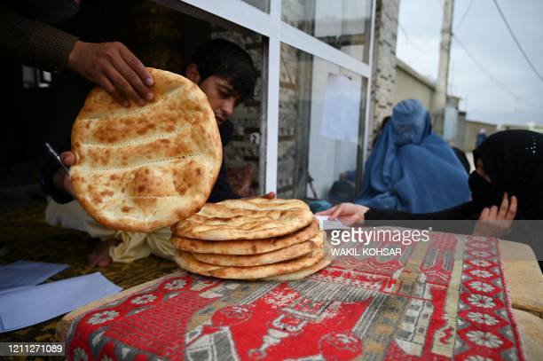 Women wait to receive free bread from the municipality outside a bakery during the Islamic holy month of Ramadan as governmentimposed a nationwide...