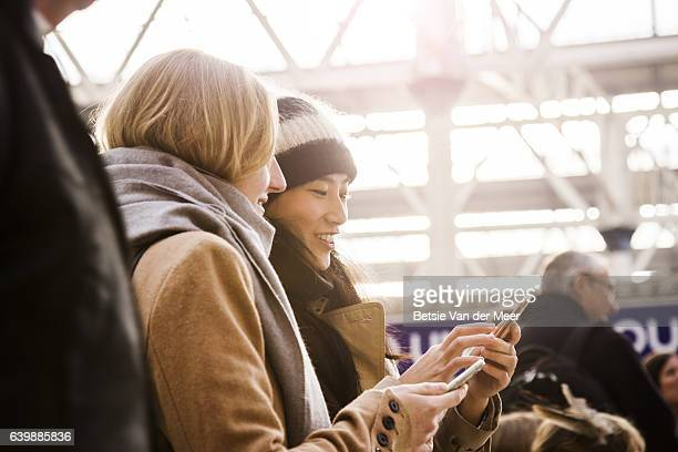Women waiting at station, looking at their phones.