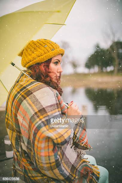 Women waiting on the river dock with umbrella