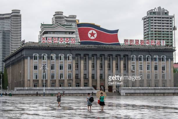 Women walk across Kim Ilsung Square as a huge North Korea flag is displayed atop the Central Committee of the Workers' Party of Korea building on...