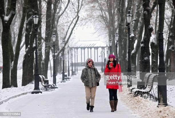 Women walk along an alley in Volodymyrska Hirka Park as it is snowing in Kyiv capital of Ukraine December 12 2018 After a spell of unusually warm...
