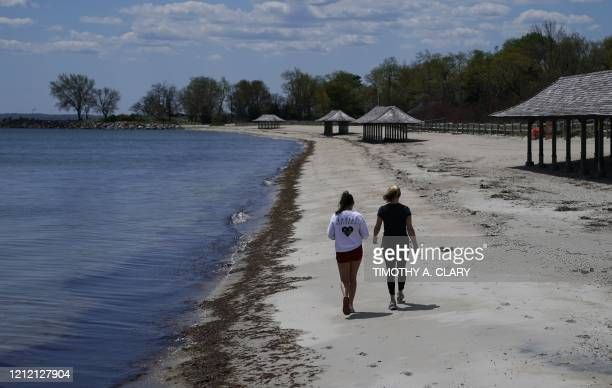Women walk along the beach on the Long Island Sound on Tod's Point in Old Greenwich Connecticut on May 7 2020 The beach and park opened partially...