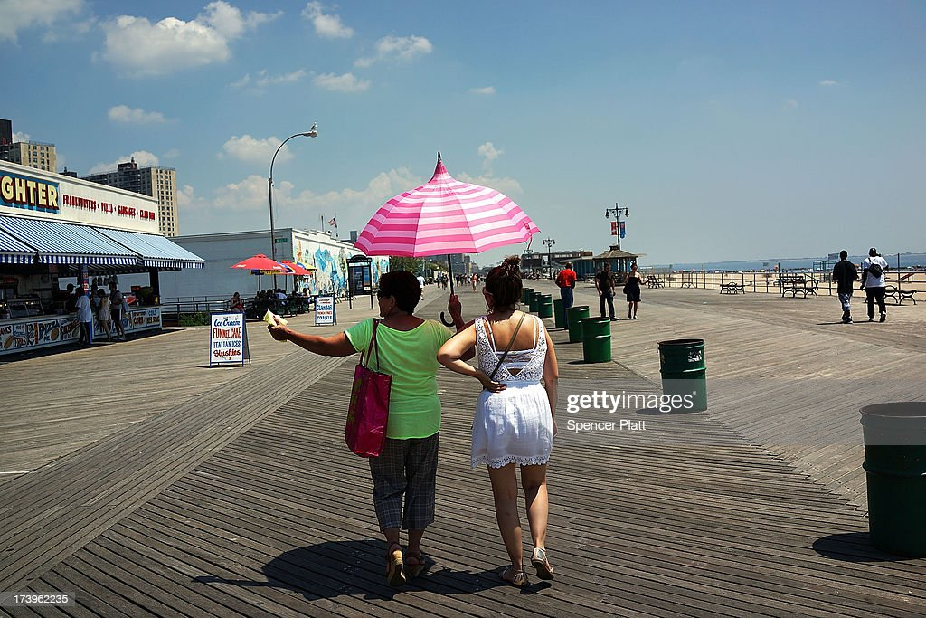 Women walk along the Coney Island boardwalk on one of the hottest weeks in recent New York City history on July 18, 2013 in New York City. With daily temperatures in the high 90's and with the heat index making it feel in the triple digits, many New Yorkers are doing what they can to stay cool. A break from the heatwave is not expected until Saturday evening at the earliest.