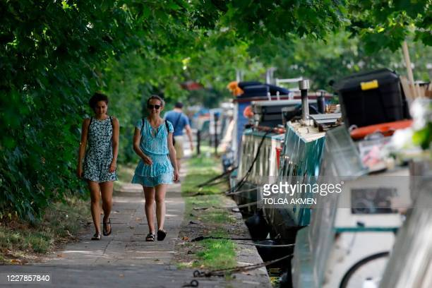 Women walk along the tow path in teh warm weather on Regent's Canal in London on July 31, 2020. - A storm warning covering much of England has been...
