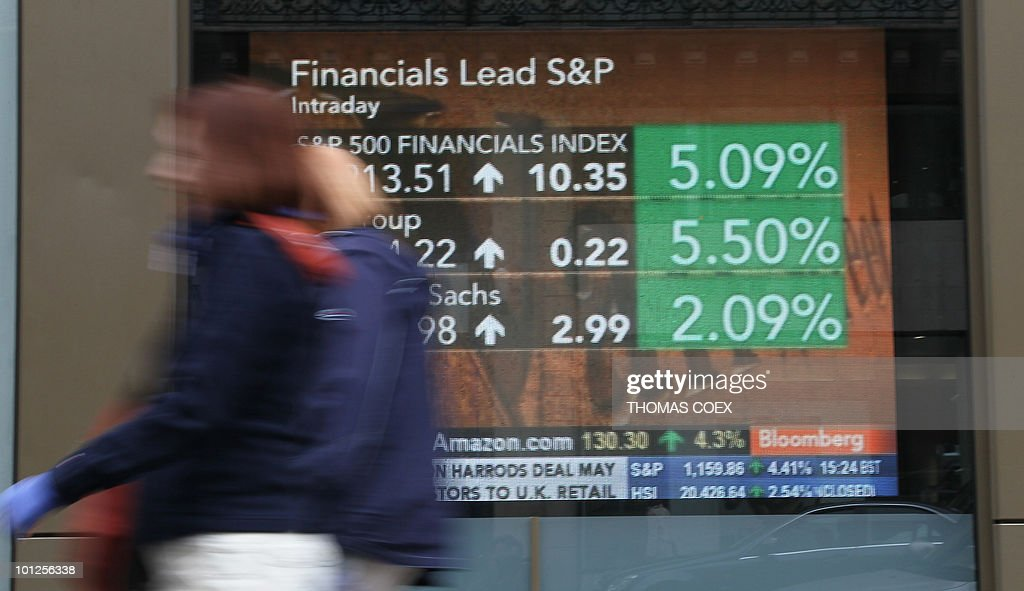 Women walk alongside a TV screen displaying stock markets information in a street of Paris, on May 10, 2010. Stock markets and the euro soared after the EU and IMF agreed a near one-trillion-dollar rescue package for the eurozone, stemming a crisis that threatened to derail global economic recovery.