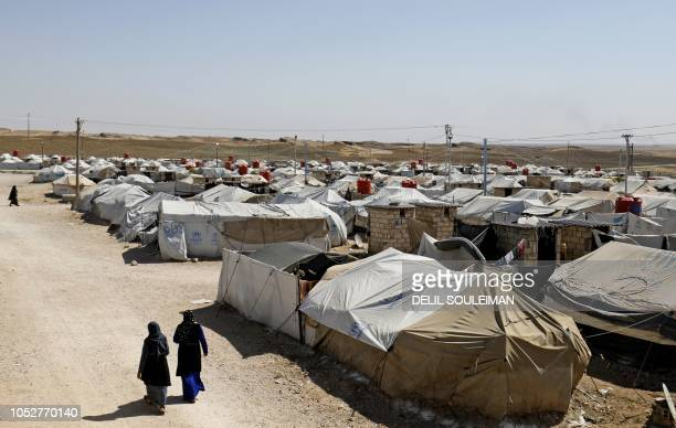 Women walk at a camp for Islamic State groupaffiliated people in the northern Syrian village of Malikiya near the border with Turkey walks with a...