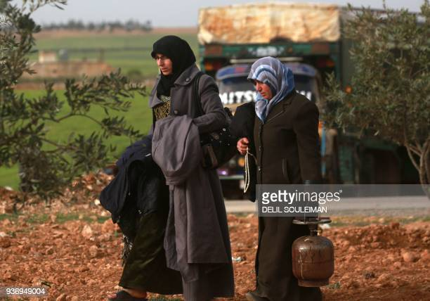 Women walk at a makeshift camp where displaced Syrians from Tal Rafaat and areas around Afrin are taking shelter near the village of Kharufiyah on...