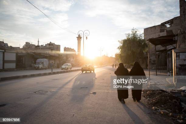 Women walk at sunset in east Aleppo. Aleppo used to be the largest city in Syria with population over 4.5 million before the war broke out in 2012....