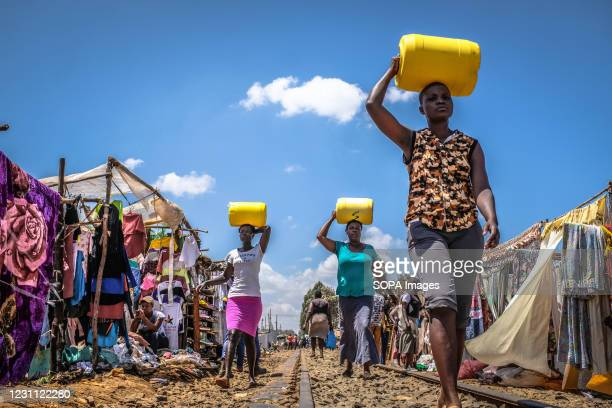 Women walk back home carrying their Water Jerrycans past the busy streets of Kibera Slums.