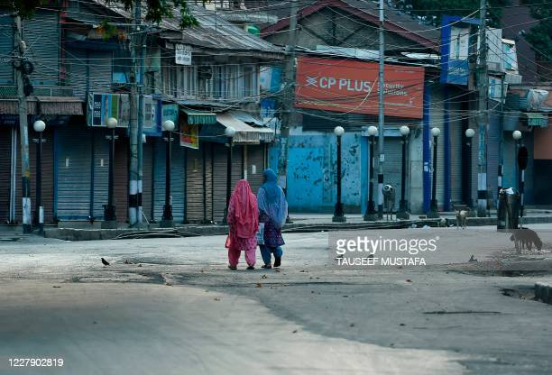 Women walk before a curfew in Srinagar on August 4, 2020. - A curfew has been imposed across Indian Kashmir just two days before the first...