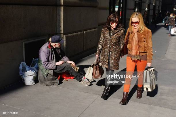 Women walk by a panhandler along Madison Avenue one of Manhattan's premier shopping and residential streets on November 1 2011 in New York City...