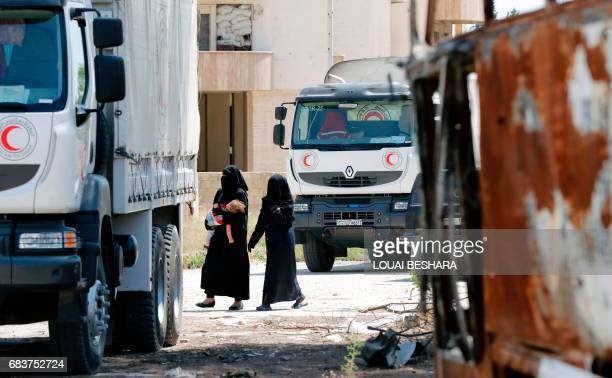 Women walk by Syrian Red Crescent vehicles in Damascus' north eastern alQaboun suburb on May 16 after the formerly rebelheld neighbourhood was...