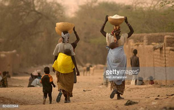 Women walk down a road with their children carrying goods in the town of Tanout, Niger. | Location: TANOUT, NIGER.