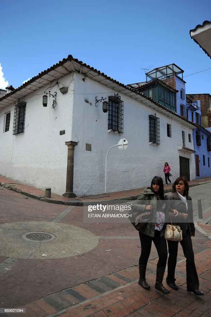 Women walk down a street in the historic neighborhood of La Candelaria in Bogota on September 17, 2009. La Candelaria is Bogota's oldest neighbourhood and the city's historical center, known for its colonial houses with wooden balconies and clay shingle roofs. AFP PHOTO/Eitan Abramovich /