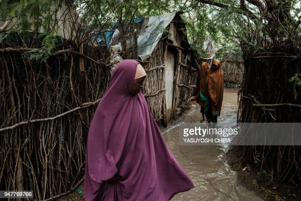 Women walk in a corridor between flooded shelters after a heavy rainy season downpour at the Dadaab refugee complex, in the north-east of Kenya, on...