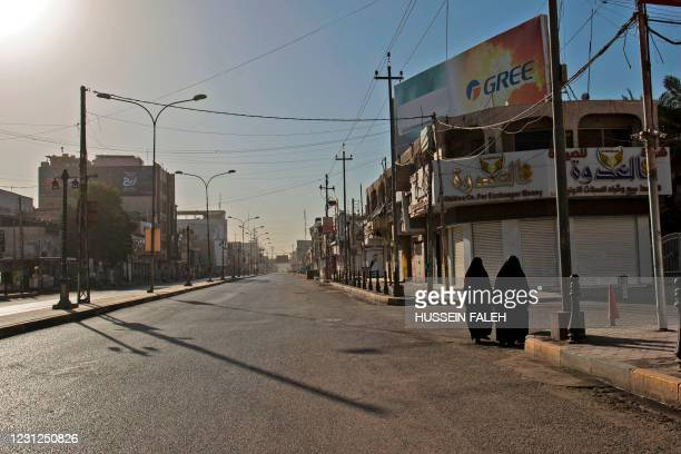Women walk in a deserted street during a new curfew to contain spike in Covid-19 cases, in the southern Iraqi city of Basra on February 19, 2021.