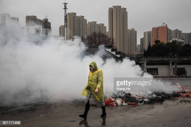 A women walk in front burning incense at the Guiyuan Temple on February 20 2018 in Wuhan Hubei province China The fifth day in the lunar new year is...