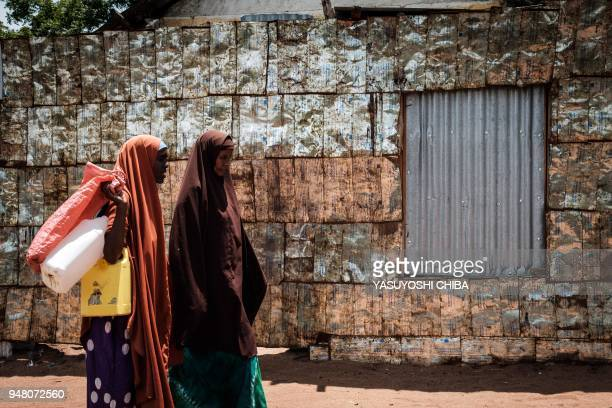 Women walk in front of a metal fence made of vegetable oil cans from USAID at the Dadaab refugee complex, northeastern Kenya, on April 18, 2018. -...