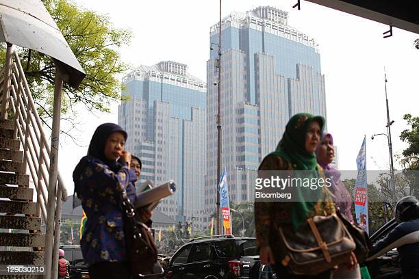 Women walk in front of the buildings of Bank Indonesia center in Jakarta Indonesia on Tuesday Oct 11 2011 Indonesia's central bank unexpectedly cut...
