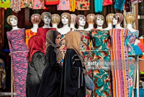 Women walk in the northern Syrian city of Raqa, the former Syrian capital of the Islamic State group, on August 21, 2019. - The Kurdish-led Syrian...