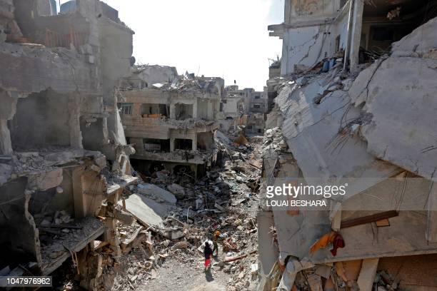 TOPSHOT Women walk in the wreckage of the Yarmuk Palestinian refugee camp in the Syrian capital Damascus as the regime began to clean the camp on...
