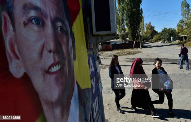 Women walk next to an election campaign poster of Kyrgyz opposition MP and presidential candidate Omurbek Babanov in the village of Vorontsovka, 20...