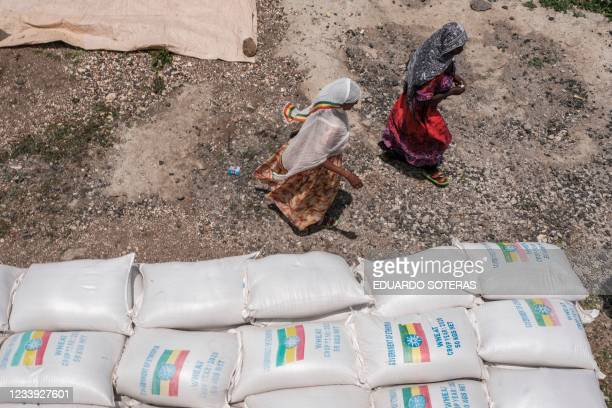 Women walk next to sacks of wheat during a food distribution organized by the Amhara government near the village of Baker, 50 kms South East of...