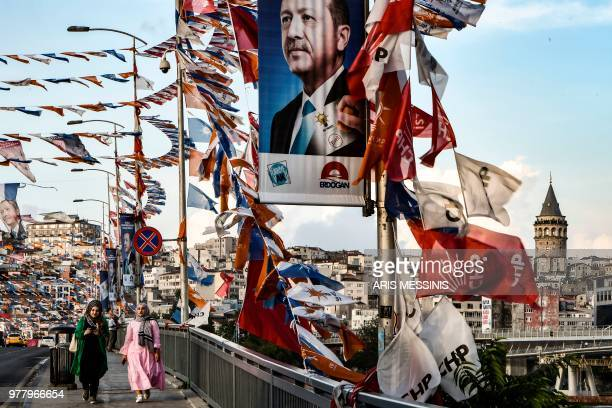 TOPSHOT Women walk on a bridge past campaign banners with the portrait of Turkey's President in Istanbul on June 18 2018 Turkey prepares for tight...