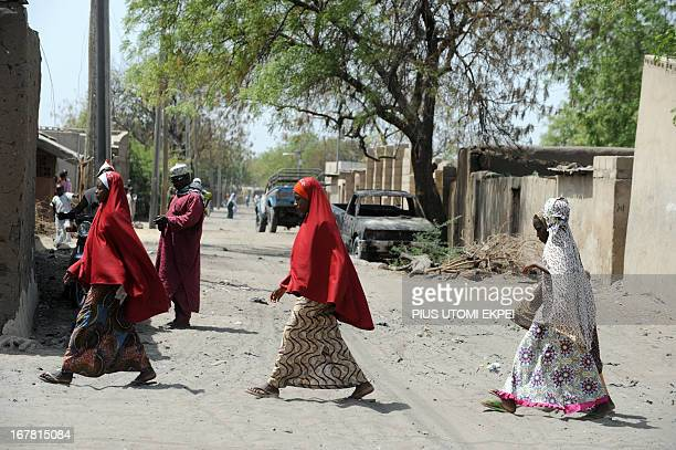 Women walk on April 30 2013 past a burnt house and vehicle after the clash between soldiers and Islamist insurgent on April 25 2013 in the remote...