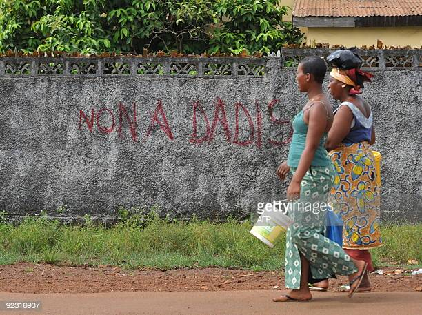 Women walk on October 22 2009 near a wall featuring in French a slogan reading No to Dadis in the Mototo neighborhood of Conakry More than 150 people...