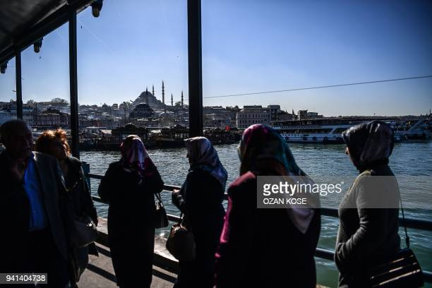 Women walk on the Galata bridge as the Suleymaniye Mosque is seen in the background during a sunny day in Istanbul on April 3 2018 / AFP PHOTO / OZAN...