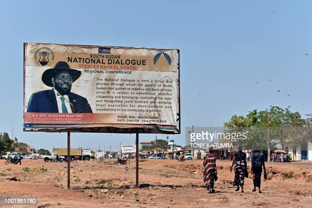 Women walk past a billboard bearing a message of unity besides an image of South Sudan President, Salva Mayardit Kiir, in Wau on February 1, 2020. -...