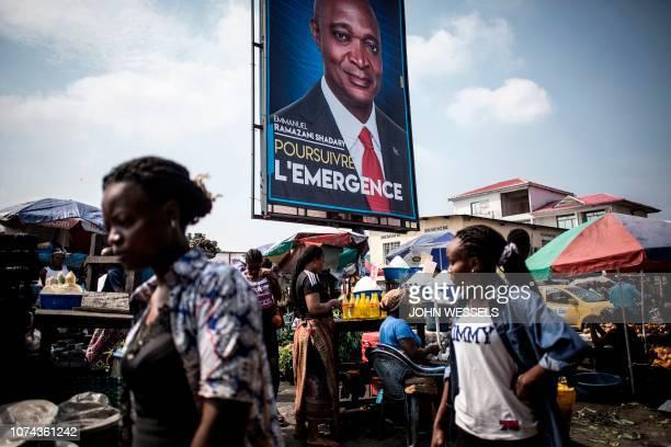 TOPSHOT Women walk past a campaign poster of the President of the Democratic Republic of the Congo Joseph Kabila's chosen successor Emmanual Ramazani...
