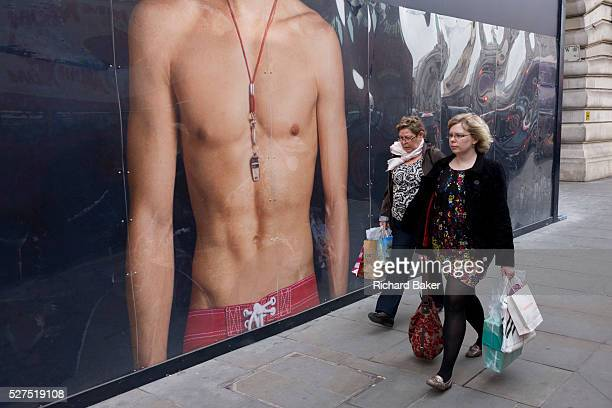 Women walk past a giant ad mural for Hollister California of a bare-chested young male model. The large image of the model wearing only swimwear and...