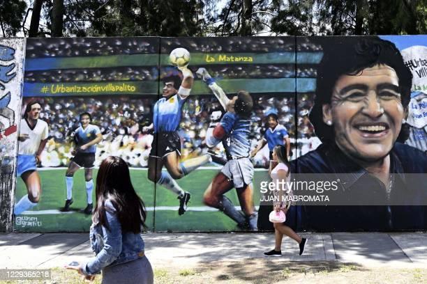 "Women walk past a mural by street artist ""Uasen"" depicting Argentine former football star Diego Maradona -current coach of Gimnasia y Esgrima La..."