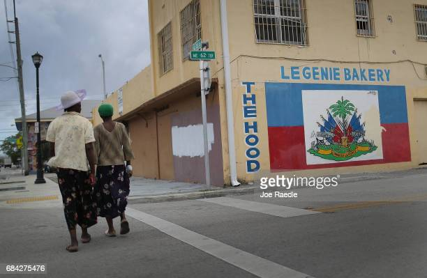 Women walk past a mural of a Haitian flag in the Little Haiti neighborhood on May 17 2017 in Miami Florida People living in the neighborhood are...
