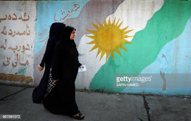 Women walk past a mural of a Kurdish flag outside a polling station in Arbil the capital of the Kurdish autonomous region in northern Iraq on May 12...