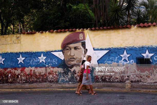 Women walk past a mural of Hugo Chávez on January 31 2019 in Caracas Venezuela Today European Parliament recognized opposition leader Juan Guaidó as...