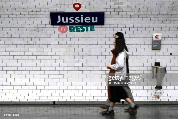Women walk past a play on words made with the Jussieu metro station reading I'm here to stay in Paris on April 1 during April Fools' Day / AFP PHOTO...